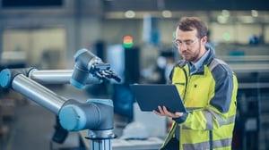 Homme programmant un robot sur un site de production industriel